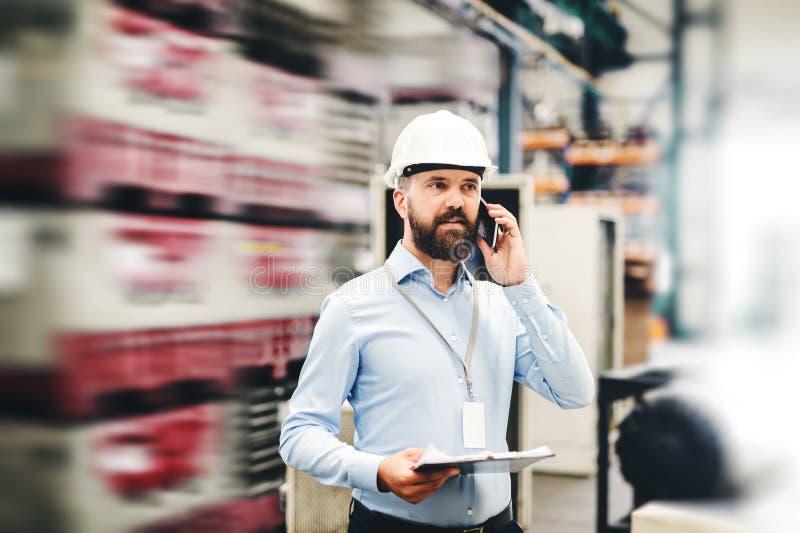 Um retrato de um coordenador industrial do homem com smartphone em uma fábrica, trabalhando fotografia de stock royalty free