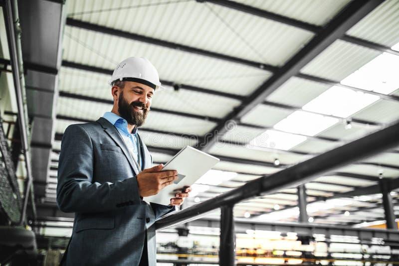 Um retrato de um coordenador industrial do homem com tabuleta em uma fábrica foto de stock royalty free