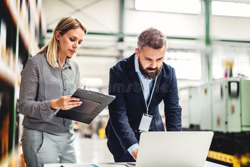 Um retrato de um coordenador industrial do homem e da mulher com portátil em uma fábrica, trabalhando imagens de stock royalty free