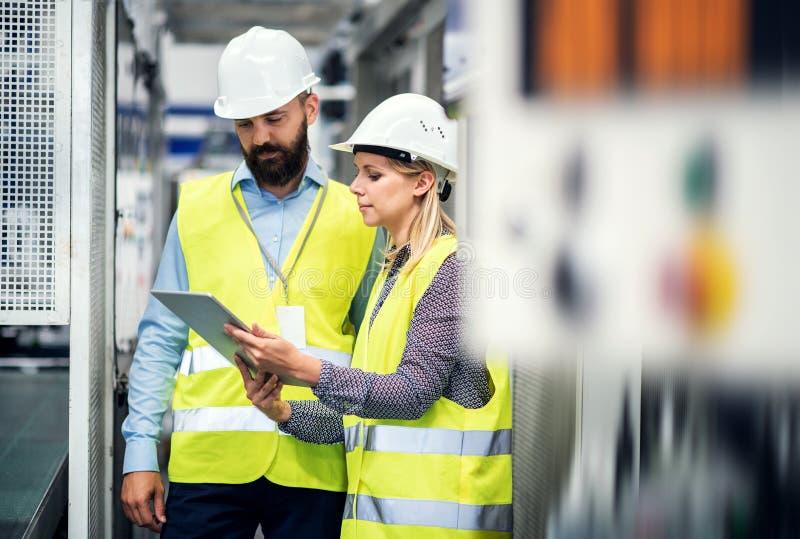 Um retrato de um coordenador industrial do homem e da mulher com tabuleta em uma fábrica, falando foto de stock royalty free