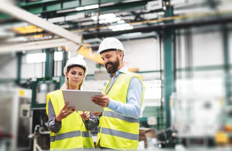 Um retrato de um coordenador industrial do homem e da mulher com tabuleta em uma fábrica, falando imagens de stock royalty free