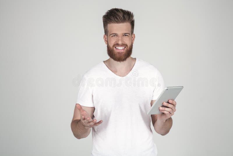 Um retrato de um homem bonito com uma barba e um penteado elegante, vestido na roupa ocasional, est? feliz com uma tabuleta e foto de stock