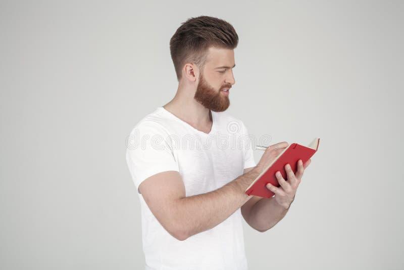 Um retrato de um homem bonito com uma barba e um penteado elegante vestidos na posi??o da roupa ocasional no perfil e foto de stock royalty free