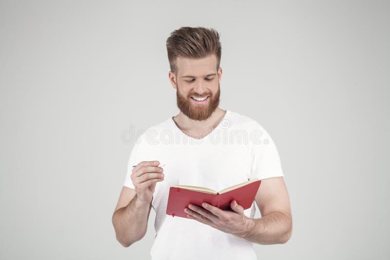 Um retrato de um homem bonito com uma barba e um penteado elegante vestidos na roupa ocasional grava alegremente algo no foto de stock royalty free