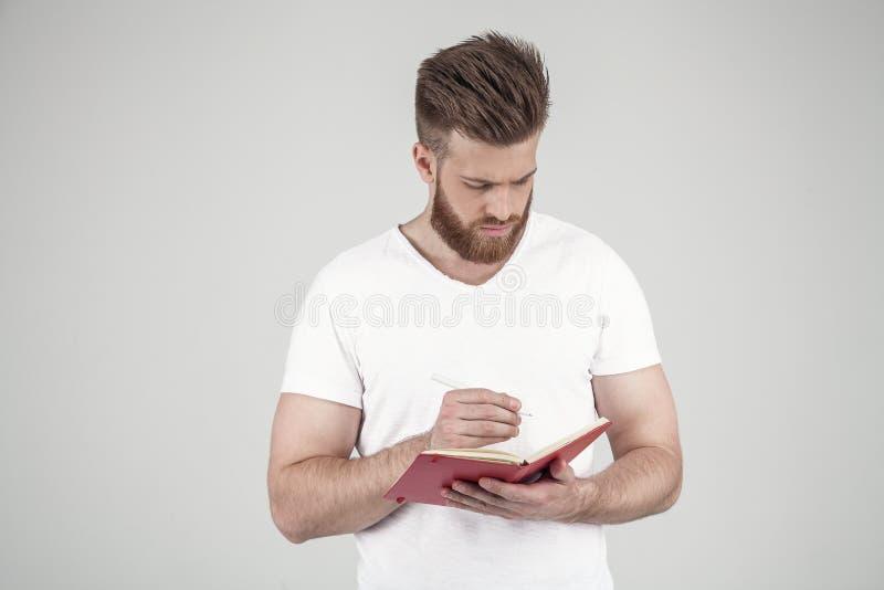 Um retrato de um homem bonito com uma barba e um penteado elegante vestidos na roupa ocasional grava pensativamente seus pensamen fotos de stock royalty free