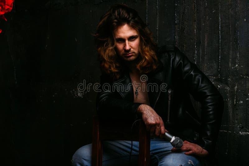 Um retrato de um homem brutal, considerável, um cantor que se sente em uma cadeira em um fundo escuro, em um Kurt de couro preto  fotos de stock royalty free