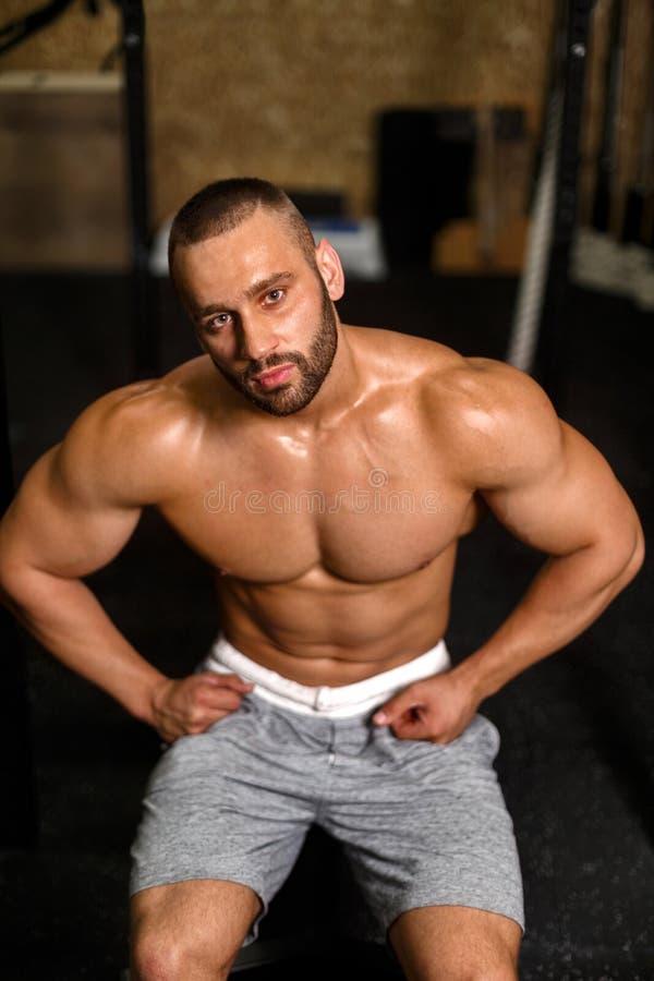 Um retrato de um homem com dobramento muscles em um fundo do gym Um halterofilista com um corpo perfeito Homem da aptidão trainin fotografia de stock royalty free