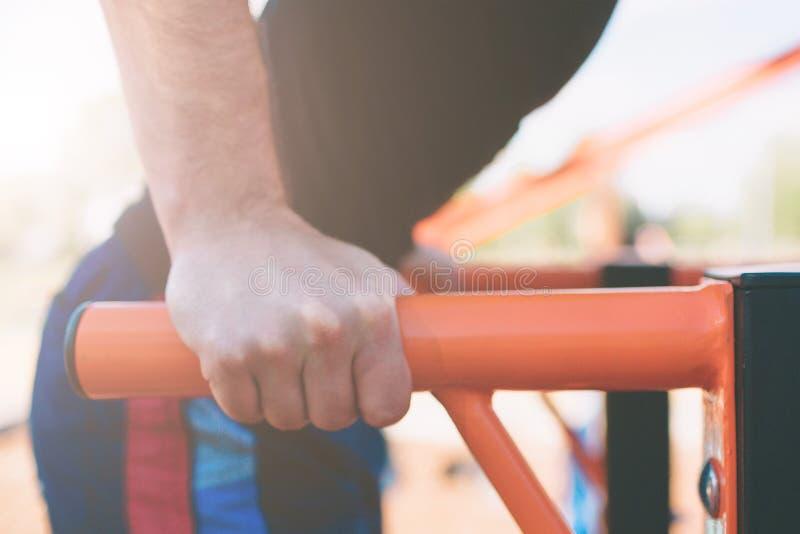 Um retrato de um homem farpado muscular focalizado no exercício preto veste fazer mergulhos em barras paralelas Equipa a aptidão  fotografia de stock royalty free