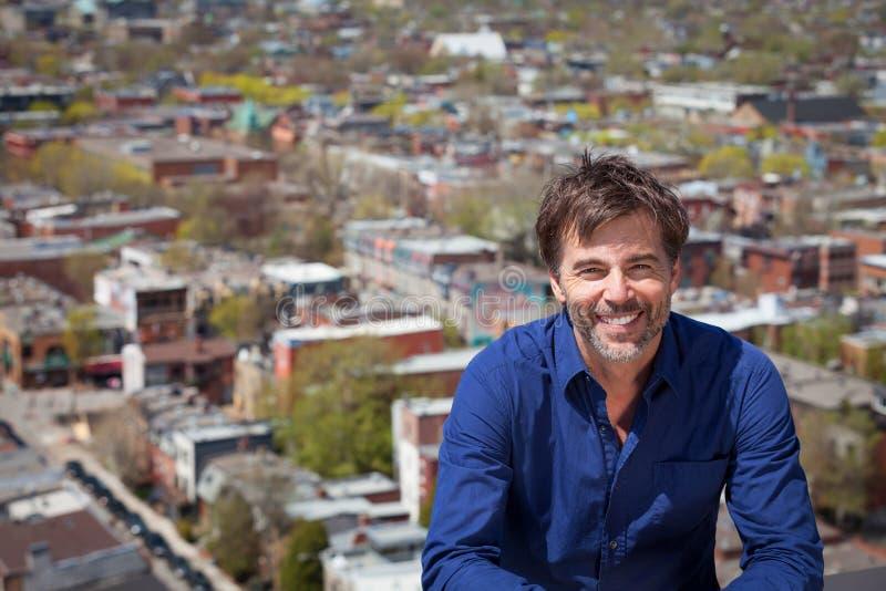 Um retrato de um homem de meia idade com uma barba curto que sorri em um fundo da cidade fotos de stock royalty free