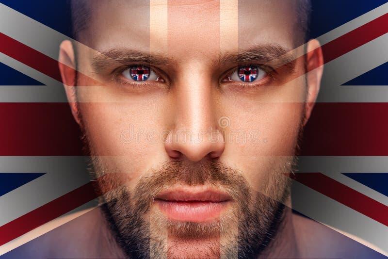 Um retrato de um homem sério novo, cujos nos olhos são refletidas as bandeiras nacionais foto de stock royalty free