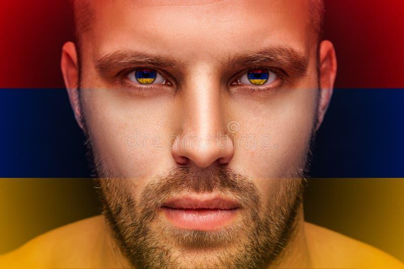 Um retrato de um homem sério novo, cujos nos olhos são refletidas as bandeiras nacionais imagens de stock