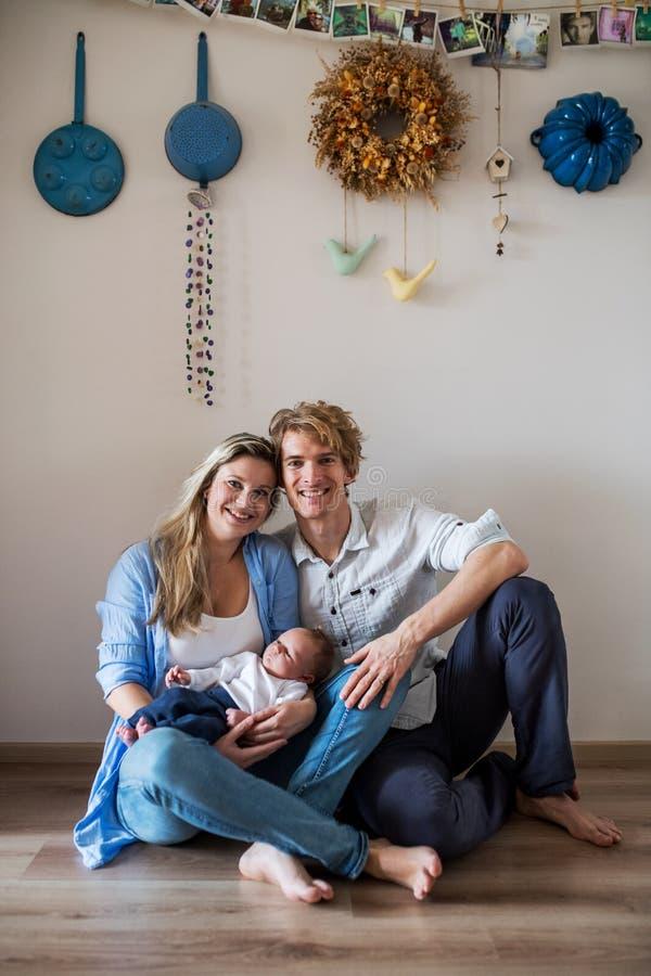 Um retrato de pais novos bonitos com um bebê recém-nascido em casa fotografia de stock royalty free