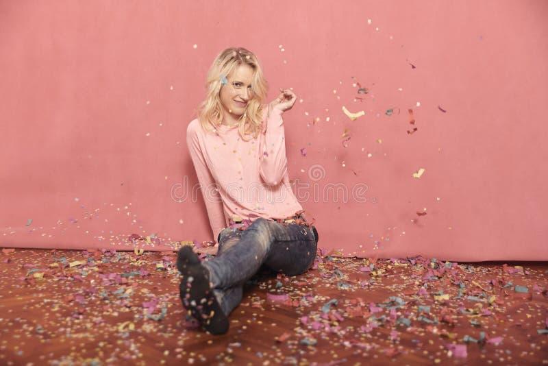 Um retrato de sorriso novo da mulher, olhando ? c?mera, sentando-se no assoalho cercado com confetes de queda, imagens de stock royalty free