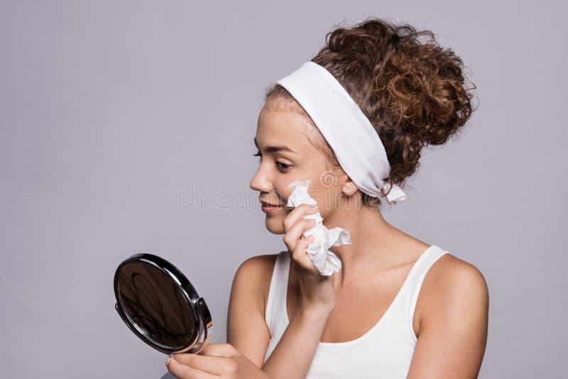 Um retrato de uma cara da limpeza da jovem mulher em um estúdio, em uma beleza e em uns cuidados com a pele imagem de stock