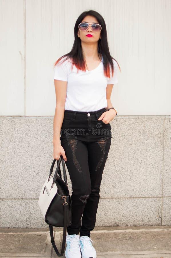 Um retrato de uma jovem mulher com a bolsa no passeio da cidade imagem de stock
