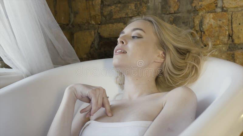 Um retrato de uma menina loura bonita na parte superior sem alças branca que senta-se no banho vazio no fundo da parede de tijolo imagens de stock royalty free
