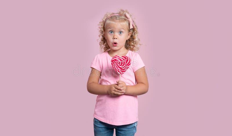 Um retrato de uma menina loura das pessoas de 3 anos bonitos em um equipamento cor-de-rosa com os olhos largos abre isolado sobre fotos de stock royalty free