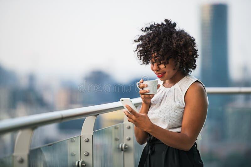 Um retrato de uma mulher com o smartphone que está em um terraço, café bebendo imagem de stock royalty free