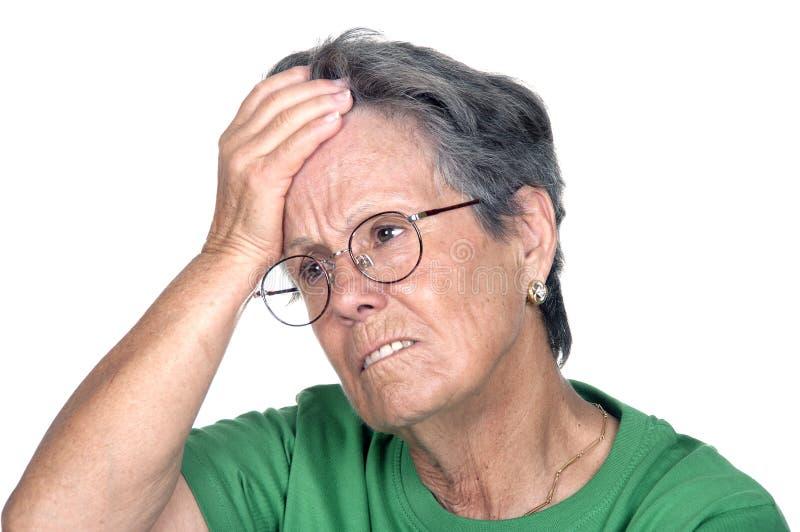 Um retrato de uma senhora superior que tem a dor de cabeça fotografia de stock