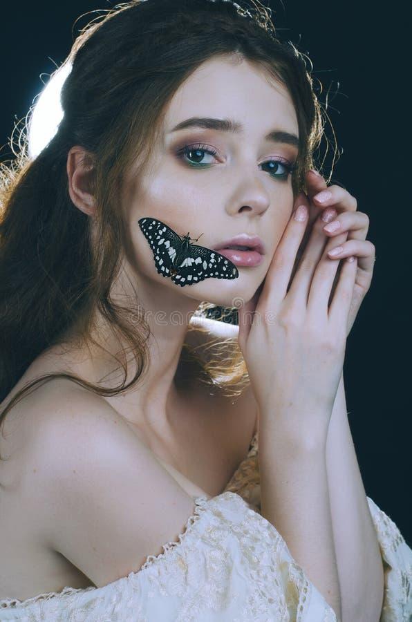 Um retrato do close-up de uma menina ruivo em um vestido do ouro do vintage, no luminoso com uma borboleta em sua cara Princesa d imagem de stock