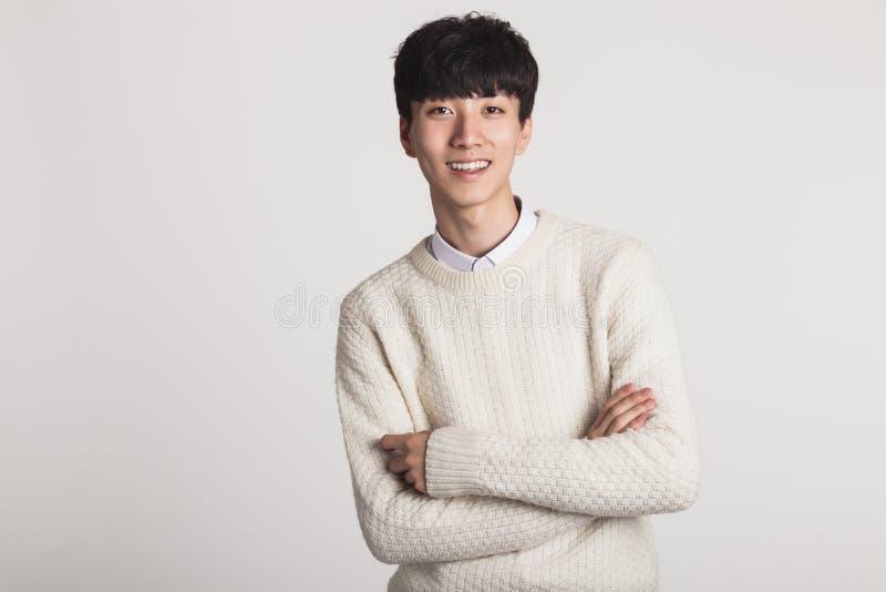 Um retrato do estúdio de um homem novo asiático que procura uma câmera com sorrisos seguros imagem de stock royalty free