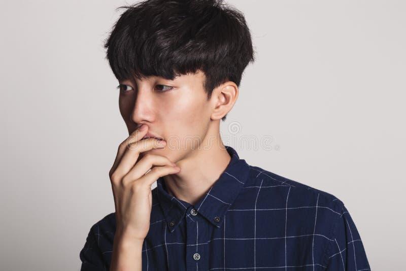 Um retrato do estúdio de um homem novo asiático que seja incomodado e profundo no pensamento imagens de stock royalty free