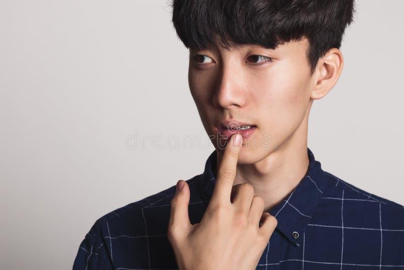 Um retrato do estúdio de um homem novo asiático que seja incomodado e profundo no pensamento foto de stock royalty free