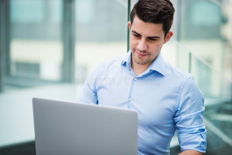 Um retrato do homem de negócios novo com o portátil que senta-se no escritório imagens de stock