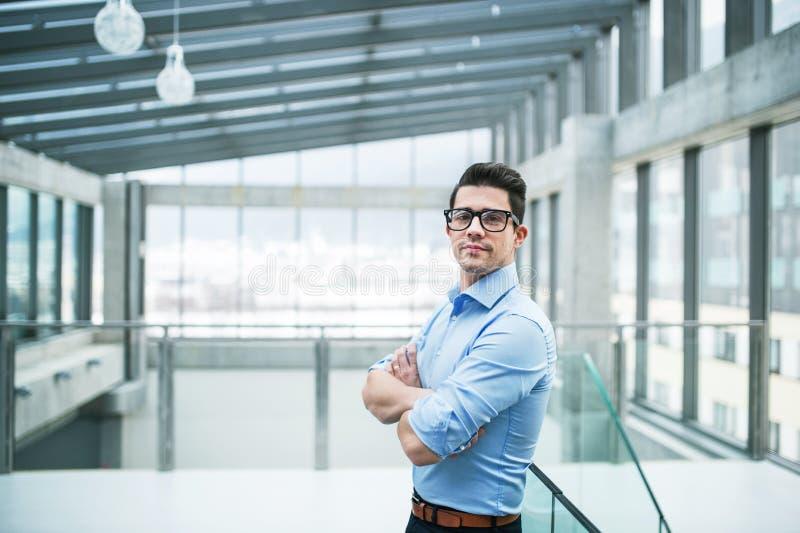 Um retrato do homem de negócios novo que está dentro em um escritório, braços cruzou-se fotos de stock