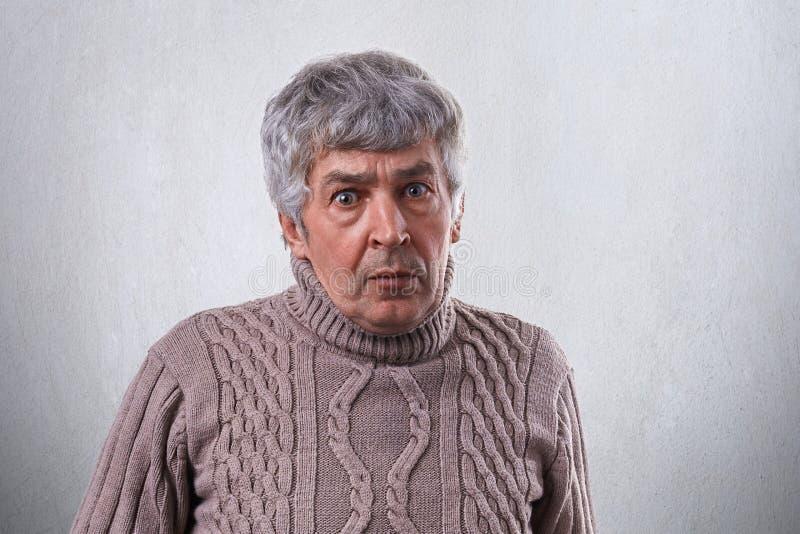 Um retrato do homem maduro surpreendido com a camiseta vestindo do cabelo cinzento que olha com os olhos largamente abertos na câ fotografia de stock royalty free