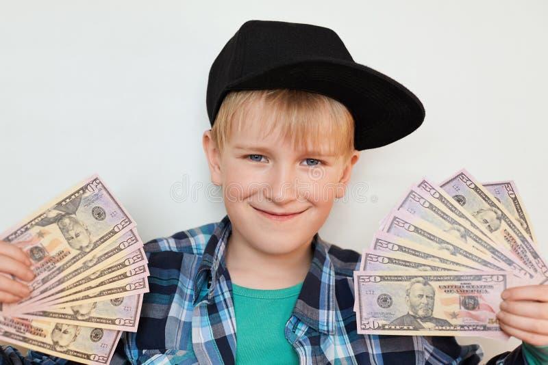 Um retrato do menino à moda pequeno deleitado no tampão preto que guarda o dinheiro em suas mãos Um homem feliz da criança que ma fotos de stock royalty free