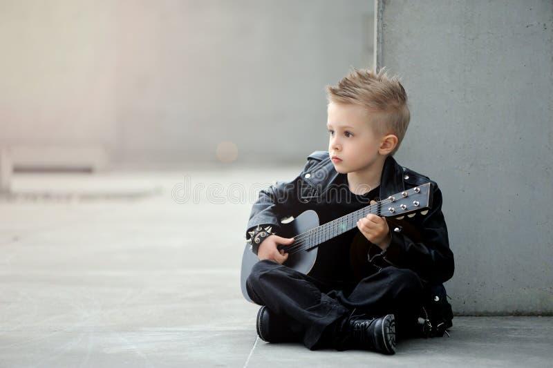 Um retrato do menino considerável no casaco de cabedal e no corte de cabelo iroquois com guitarra fotos de stock