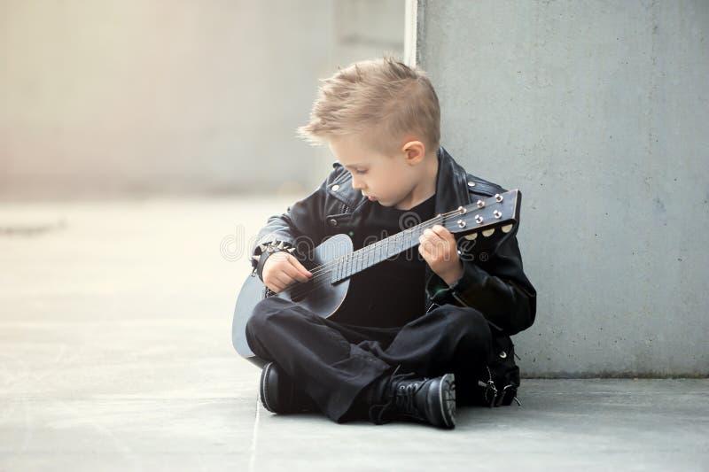 Um retrato do menino considerável, sensível, triste no casaco de cabedal e do corte de cabelo iroquois fotografia de stock royalty free