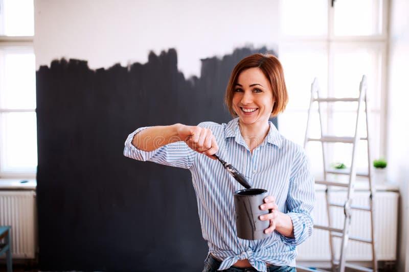 Um retrato do preto da parede da pintura da jovem mulher Uma partida da empresa de pequeno porte foto de stock