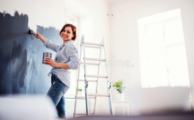 Um retrato do preto da parede da pintura da jovem mulher Uma partida da empresa de pequeno porte imagens de stock