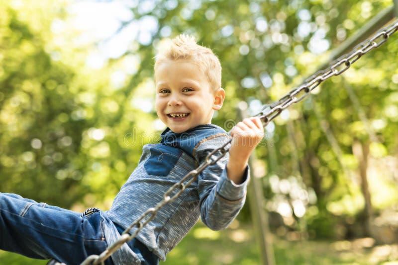 Um retrato do rapaz pequeno de sorriso feliz no balanço imagem de stock