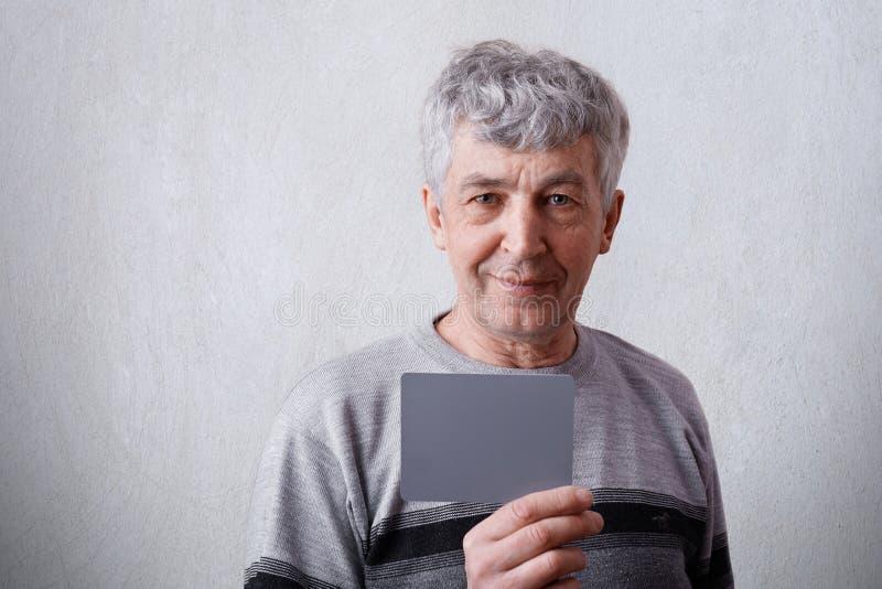 Um retrato horizontal do homem maduro atrativo com cabelo e os enrugamentos cinzentos vestiu-se na camiseta ocasional que guarda  imagem de stock