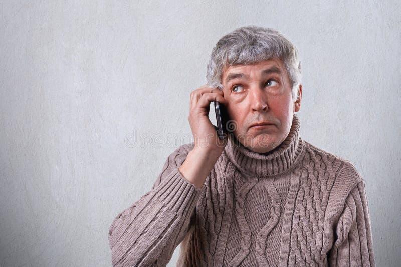 Um retrato horizontal do homem maduro com cabelo e os enrugamentos cinzentos vestiu-se na camiseta morna que guarda o telefone ce foto de stock