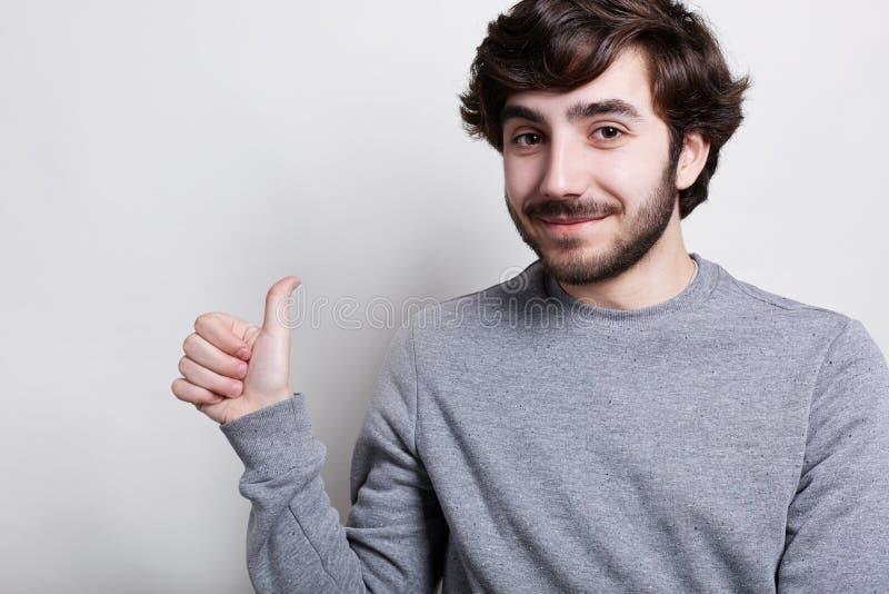 Um retrato horizontal do moderno farpado à moda com o penteado na moda que é positivo vestiu-se na camiseta cinzenta ocasional qu imagem de stock royalty free