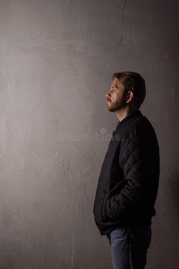 Um retrato impassível de um homem em um revestimento preto e nas calças de brim que estão perto de uma parede imagens de stock