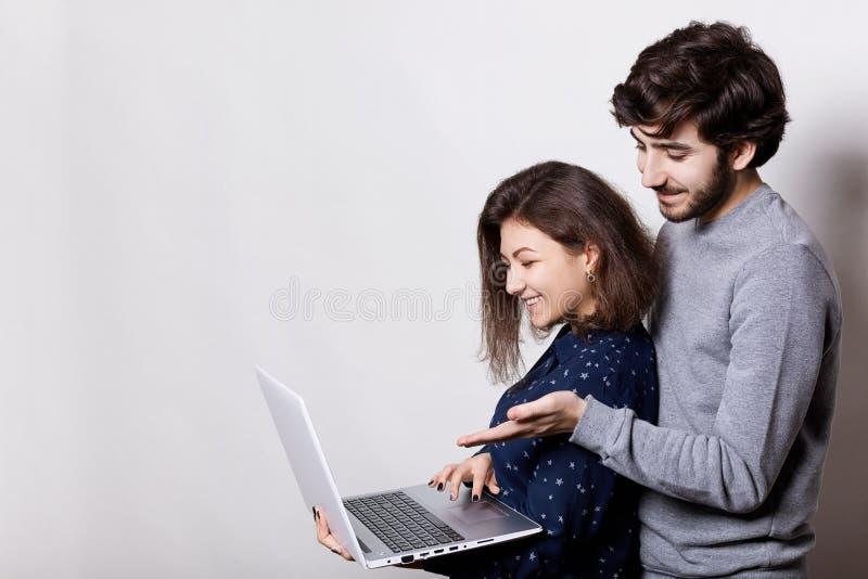 Um retrato lateral da posição em linha de observação dos vídeos dos pares bonitos perto de se que guarda o portátil usando o rádi fotos de stock royalty free