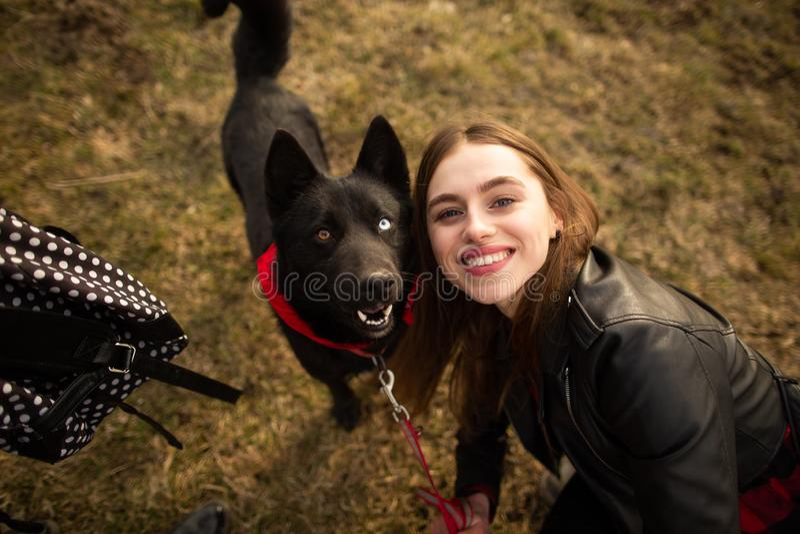 Um retrato maravilhoso de uma menina e de seu cão com olhos coloridos Os amigos estão levantando na costa do lago fotos de stock royalty free