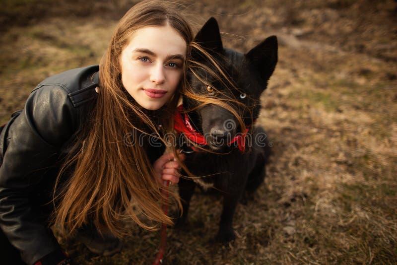 Um retrato maravilhoso de uma menina e de seu c?o com olhos coloridos Os amigos est?o levantando na costa do lago imagens de stock royalty free