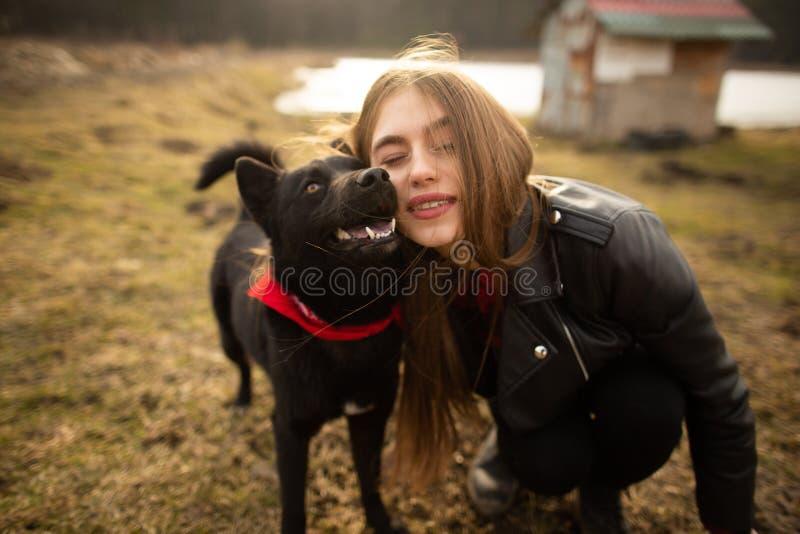 Um retrato maravilhoso de uma menina e de seu c?o com olhos coloridos Os amigos est?o levantando na costa do lago imagem de stock