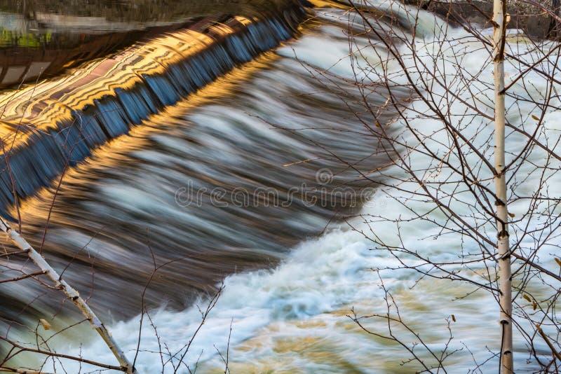 Um rio de borbulhagem com um rapid e uma reflexão e dois vidoeiros de prata novos na mola adiantada imagem de stock