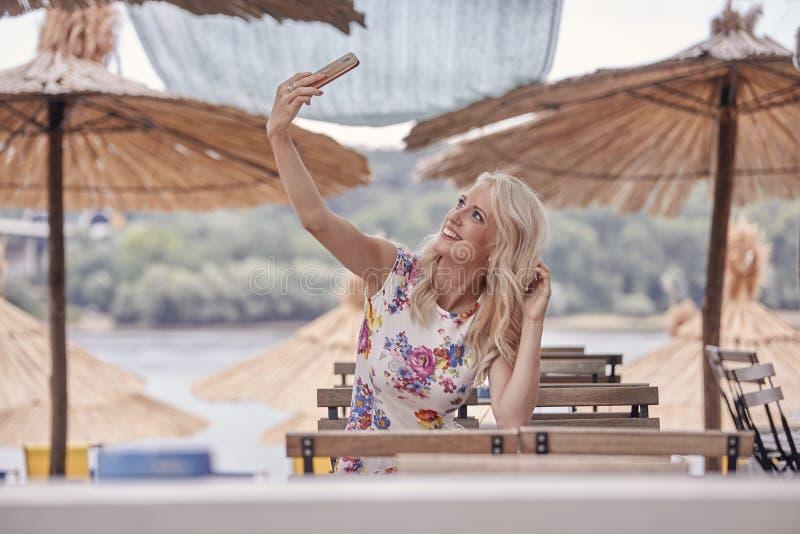 Um riso da jovem mulher, 25 anos velho, olhando acima acima ao smartphone que faz o autorretrato do selfie, photograping foto de stock royalty free