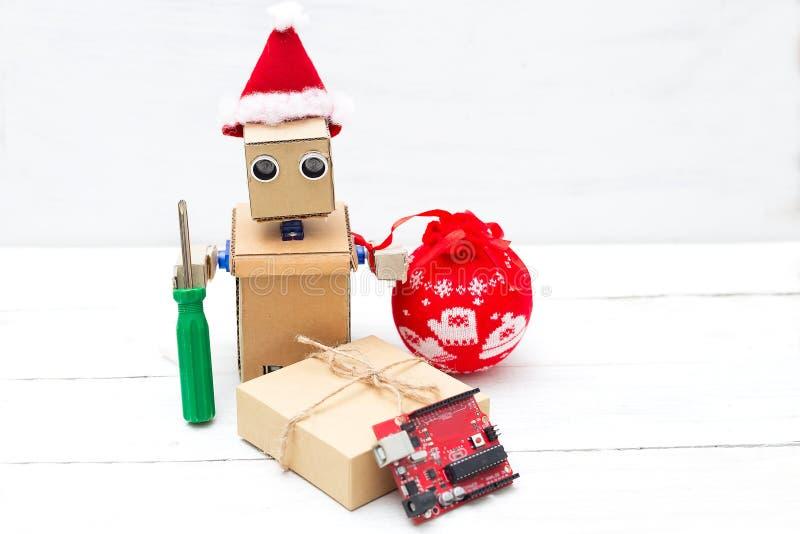 Um robô em um chapéu de Santa guarda uma chave de fenda e um brinquedo do Natal dentro foto de stock