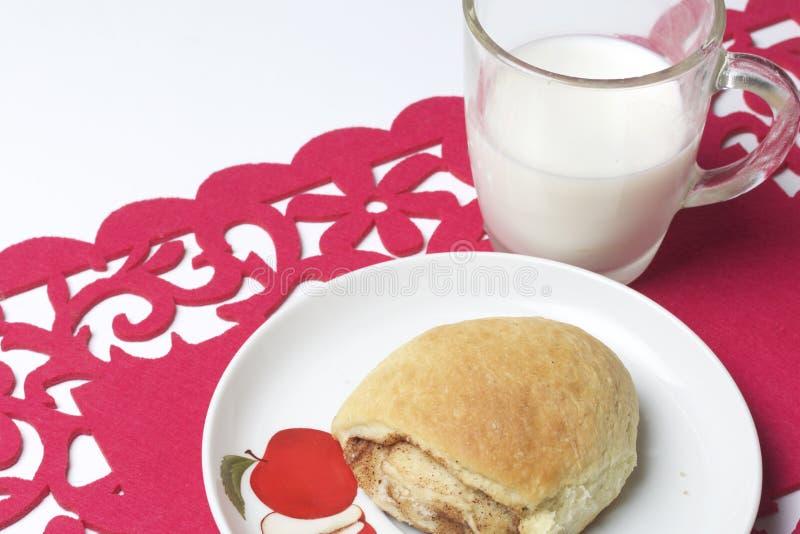Um rolo de canela encontra-se em uma placa Está próximo um vidro do leite Todo o isto em um guardanapo a céu aberto vermelho foto de stock