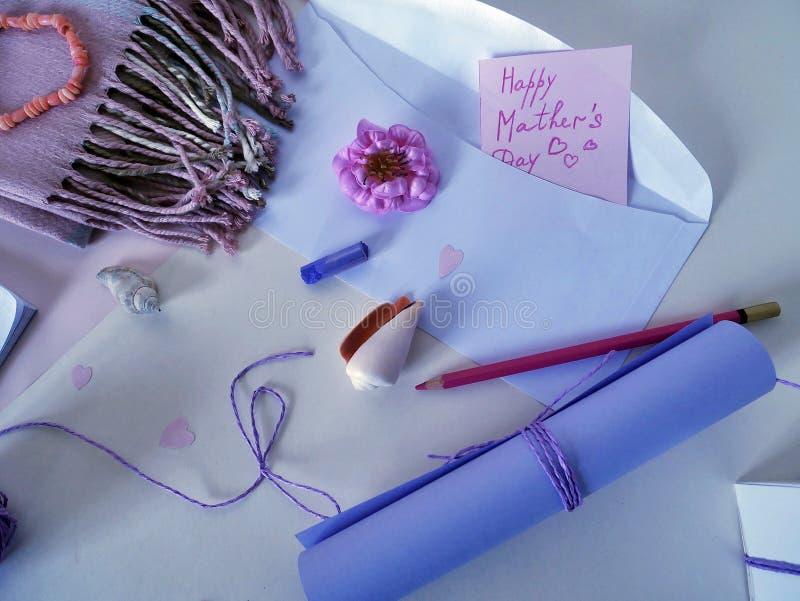 Um rolo do papel ultravioleta, da flor cor-de-rosa, do pastel pastel ultravioleta, do bloco de notas e do cartão para serir de mã foto de stock