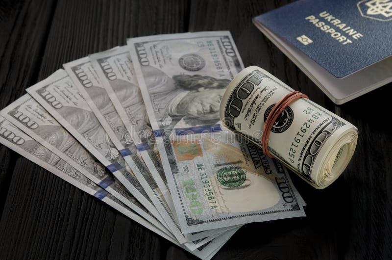 Um rolo grosso de cem cédulas velhas do dólar amarrou um elástico vermelho encontra-se na suiça de cem notas de dólar novas foto de stock royalty free
